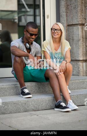 lachende junge freunde im sommer in der stadt mit mobiltelefon