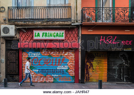 A young man walking past colorful shops along Rue des Augustins in Perpignan, France. - Stock Photo