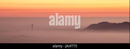 Hazy sunset over Golden Gate Bridge, San Francisco. - Stock Photo