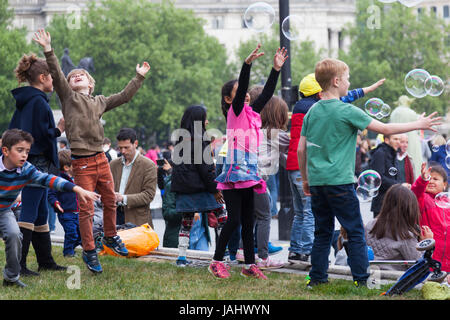 London, United Kingdom, 6 may 2017: children have fun with giant soap bubbles on trafalgar square in front of national - Stock Photo