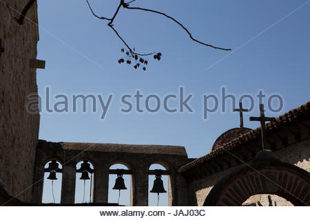 Crosses and bells atop a building at the Mission San Juan Capistrano in California. The Mission was founded in 1776. - Stock Photo