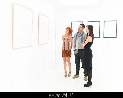 group of young caucasian people standing in front of large empty frames displayed on white walls, contemplating - Stock Photo