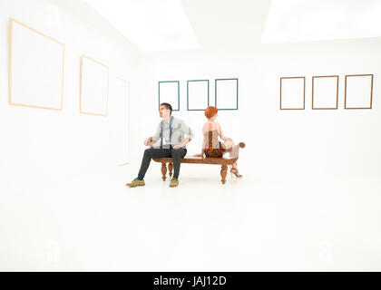 woman and man sitting on a wooden bench looking at empty frames displayed on white walls in front of them - Stock Photo