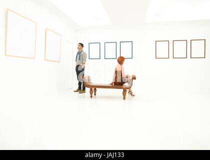 woman and man contemplating empty frames displayed on white walls - Stock Photo