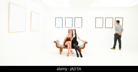 front view of women sitting on a bench whispering secrets, in a white rom, with empty frames displayed on walls - Stock Photo