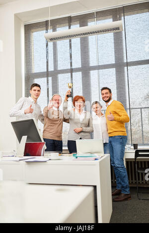 Successful business team with thumbs up holds winner cup trophy