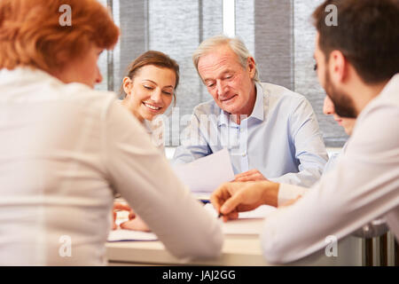 Senior as consulting man with experience gives advice in meeting - Stock Photo