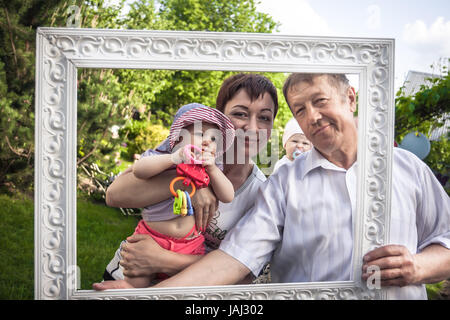 Happy family portrait of cheerful grandfather with his daughter and grandchild during outdoors party - Stock Photo