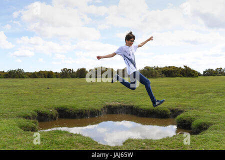 Young boys play jumping over puddles in the New Forest - Stock Photo