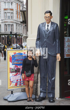 England,London,Picadilly Circus,tourist and oversized character before 'Ripley's Believe it or not!' museum, - Stock Photo