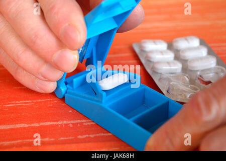 Tablette wird mit Tablettenschneider geteilt - Stock Photo