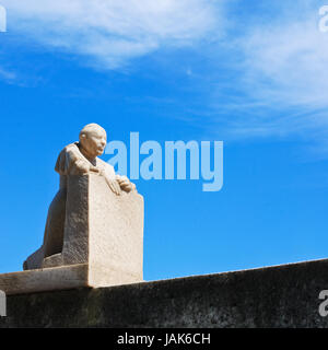 statue kneels and prays in the confessional - Stock Photo