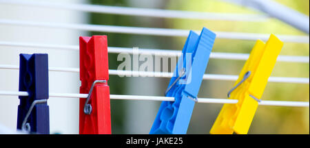 colorful pegs on a drying rack - Stock Photo