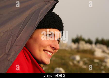 Eine junge Frau schaut beim Zelten aus dem Zelt dem Sonnenuntergang entgegen - Stock Photo