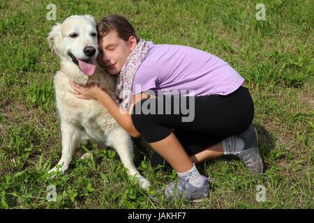 Ein Mädchen schmust mit einem Hund auf einer Wiese - Stock Photo