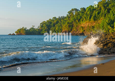 Wave crashing at sunset on the beach by Corcovado national park in the Osa Peninsula by the Pacific Ocean in Costa - Stock Photo