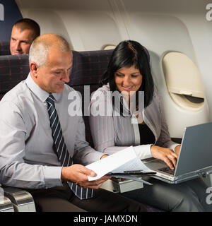 Businesspeople working on computer during flight airplane cabin passenger travel - Stock Photo