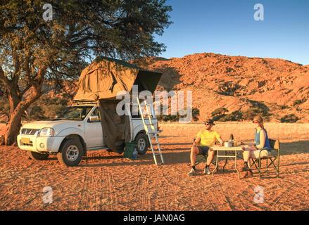 Couple camping in desert having dinner. Orange sunset sunrise light. - Stock Photo