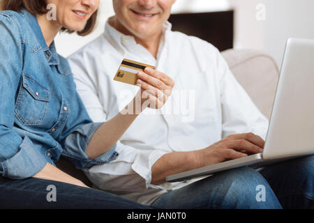 Mature Couple connected with laptop and shopping online - Stock Photo