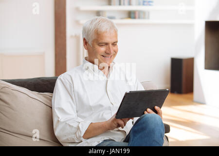 Smiling mature man sitting on a sofa using a tablet pc  in a living room - Stock Photo