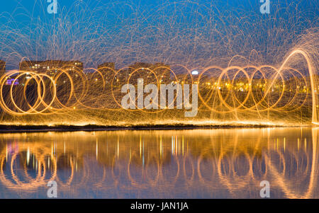 Hot Golden Sparks Flying from Man Spinning Burning Steel Wool near River with Water Reflection. Long Exposure Photography - Stock Photo