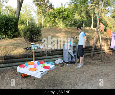 Young camper prepares dinner in the campsite of the resort in summer - Stock Photo