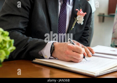 marriage elegant groom signing german wedding register, holding pen and official document couple - Stock Photo