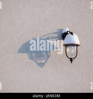 Outdoor lamp covered with snow and its shadow on the wall - Stock Photo