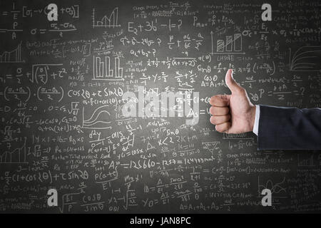 Women hand thumbs up sign in front of mathematical formulas drawn on blackboard - Stock Photo