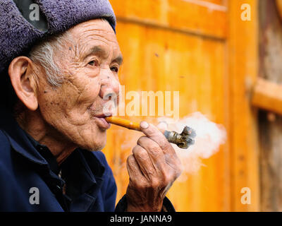 ZHAOXING, CHINA - 11 NOVEMBER 2010:  Old Chinese resting on the doorstep of his cottage smoking a pipe in the village - Stock Photo
