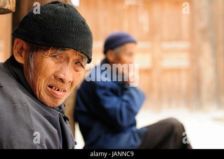 ZHAOXING, CHINA - 11 NOVEMBER 2010:  Old Chinese resting on the doorstep of his cottage in the village Zhaoxing - Stock Photo