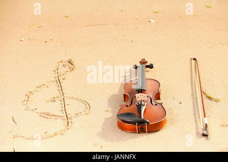Violin string and g treble clef shape on sandy beach. Love of music concept - Stock Photo