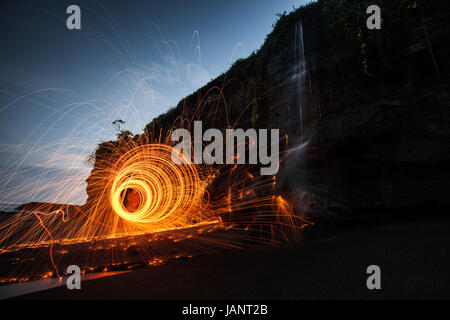 Circles of light created by light painting with burning wire wool at a beautiful spot on a Bali beach with a waterfall - Stock Photo