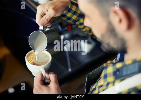 Waiter doing heart shape in coffee while pouring milk - Stock Photo