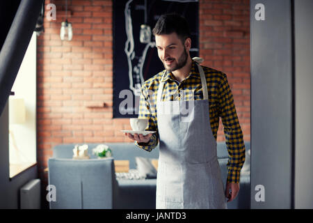 Young waiter serving cup of coffee - Stock Photo