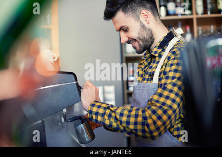 Side view of waiter using coffee maker - Stock Photo