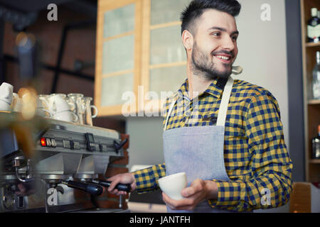 Waiter serving delicious cup of coffee - Stock Photo