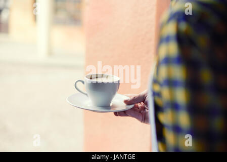 Low angle view of bartender carrying coffee - Stock Photo