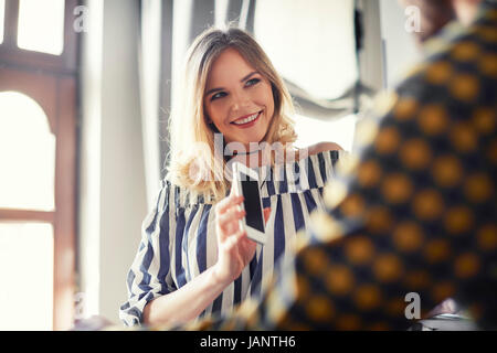 Female customer using mobile phone - Stock Photo