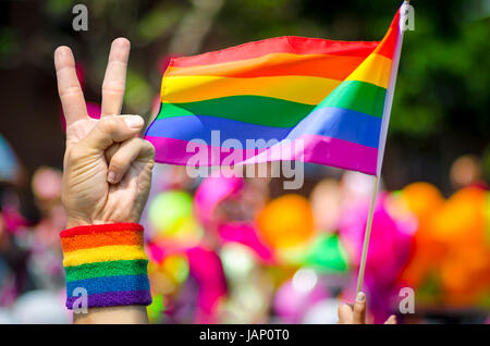 Supporting hand makes peace sign in front of a rainbow flag flying on the sidelines of a summer gay pride parade - Stock Photo