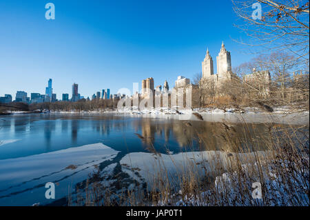 Scenic view of the Upper West Side skyline reflecting in the ice of the frozen Central Park lake after a winter - Stock Photo