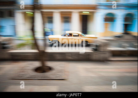 Slow shutter speed motion blur view of passing classic american car in Havana, Cuba - Stock Photo