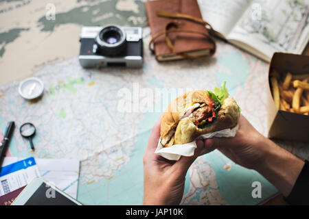 Closeup of hands holding hamburger over map background - Stock Photo