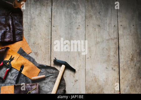 Aerial view of leather crafting with tools on wooden table - Stock Photo