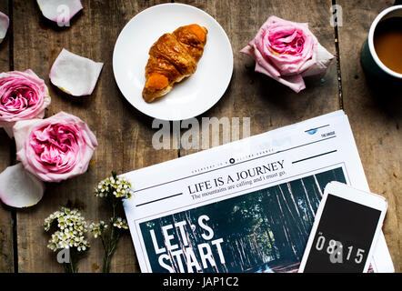 Aerial view of croissant and newspaper with roses decoration on wooden table - Stock Photo