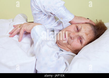 Picture of an elderly woman having a migraine, lying in bed - Stock Photo