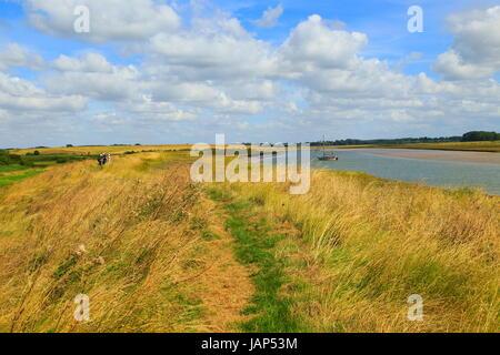 Butley Creek river landscape, Boyton, Suffolk, England, UK people walking footpath on flood defence bank wall - Stock Photo