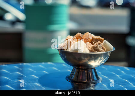 Close up white and dark cane sugar cubes in metal bowl - Stock Photo