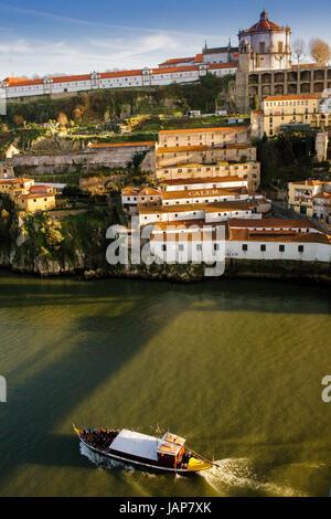 Rabelo boat hauls tourists on Douro River neath Calem wine lodges and Mosteiro da Serra do Pilar, Oporto, Portugal - Stock Photo
