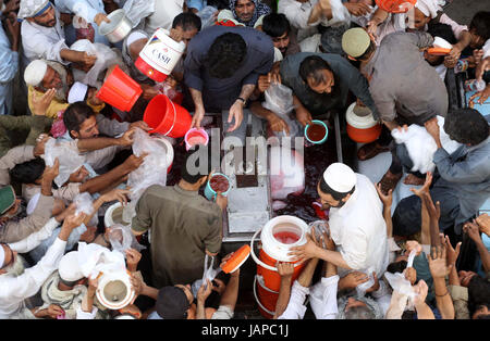 Watermelon juice is being distributing among Muslims as almsgiving by philanthropist during Holy Month of Ramzan - Stock Photo